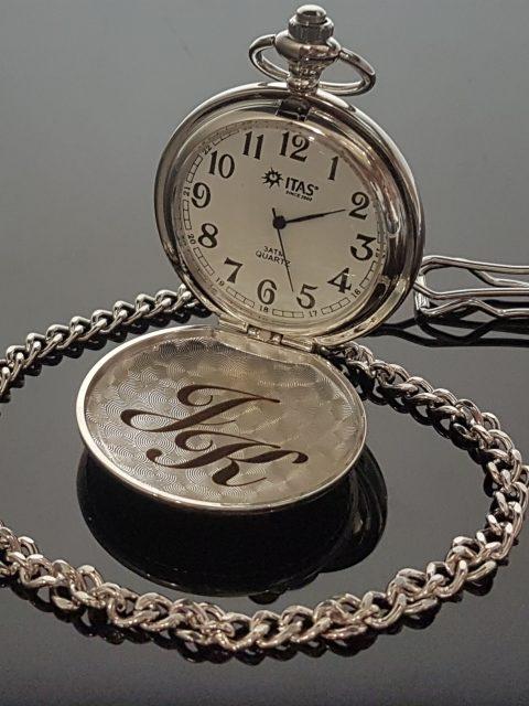 Gravírované iniciály na vreckových hodinkách ITAS